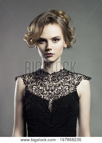 Studio fashion photo of beautiful young lady on black background. Classic studio portrait. Elegant hairstyle