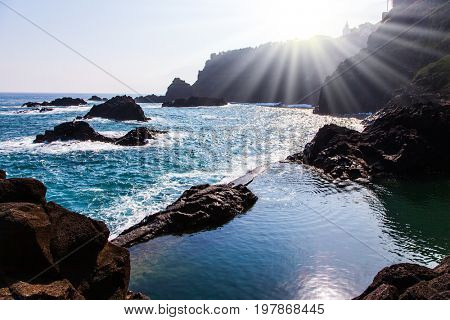 The bright sun illuminates the stony shore of the Atlantic ocean. Small bay with smooth water. Volcanic island of Madeira. The concept of exotic and ecological tourism