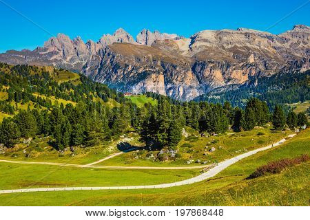 Windy sunny autumn day. Travel to South Tyrol, Dolomites. The concept of extreme and ecological tourism. The picturesque road on the Sella Pass