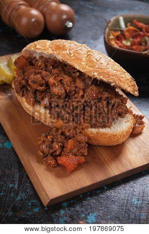 Sloppy Joe's ground beef sandwich served on wooden board