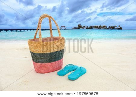 Bag and flip-flops on sea beach. Summer vacation concept