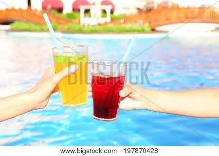 Hands of young women clinking glasses with cocktails near pool