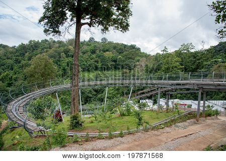 Roller coaster tracks in the green forest at Chiang mai Province Thailand.