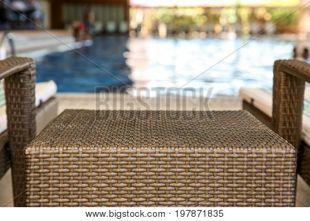 Rattan table and chaise longues near modern swimming pool, closeup