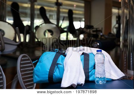Bag with personal things, towel and bottle of water in gym