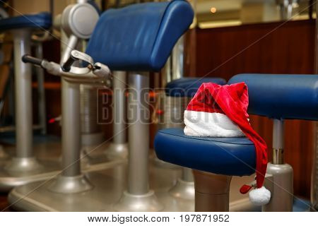 Santa hat on modern fitness machine in gym