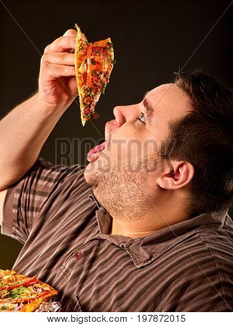 Diet failure of fat man eating fast food slice pizza on plate. Close up of breakfast for hungry overweight person who spoiled healthy food. Obesity due to eating bad foods.
