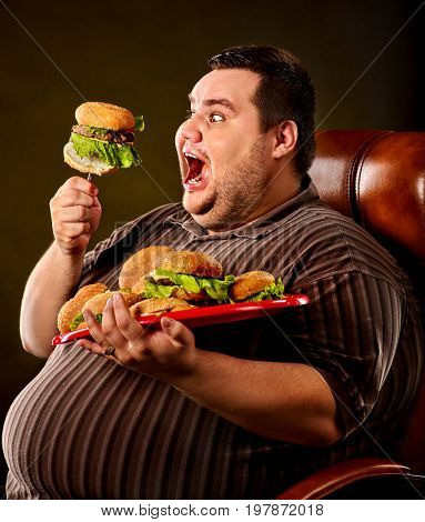 Diet failure of fat man eating fast food hamberger. Happy smile overweight person who spoiled healthy food by eating huge hamburger on fork. He's carrying a burger tray, on a leather chair.