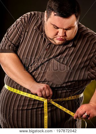 Man belly fat with tape measure weight loss around body on black background. Obesity due to eating bad foods.