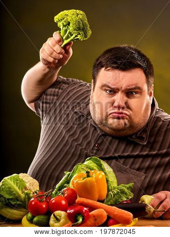 Diet fat man eating healthy food. Health breakfast with vegetables broccoli for overweight person. Male trying to lose weight but he can no longer eat cabbage. He is trying to go on a diet.