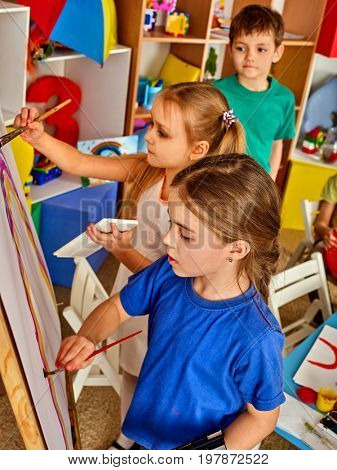 Children painting finger on easel. Group of kids girl and boy with teacher learn paint in class school. Child picture on background. Students draw a rainbow. Preparation for an art exhibition.
