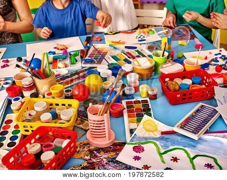 Kindergarten tables with painting brush and teacher in interior. Preschool class waiting kids. Playroom with a lot of object on table. Preparation for an art exhibition. Top view.