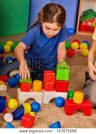 Children building blocks in kindergarten. Group kids playing toy on floor. Top view of interior preschool. Kid is keen on playing dice. She does not get along with other children.