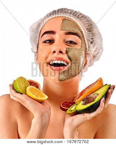Avocado clay face mask. Woman in medical hat holding half of green fruit with stones isolated background. Facial beautiful procedure concept. Girl is enjoying the rest in the spa salon.
