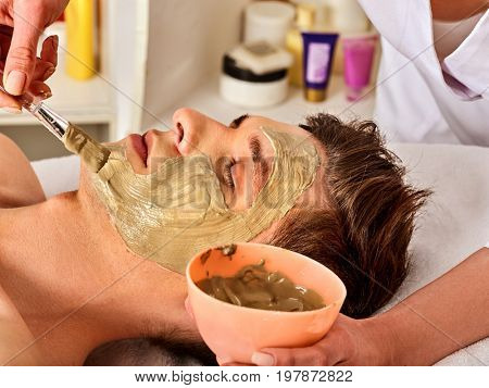Mud facial mask of man in spa salon. Massage with clay full face. Therapeutic mud for the face. Apply a mask on face with a brush. Beautician with bowl therapeutic procedure isolated background.