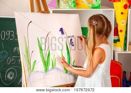 Children painting finger on easel. Group of kids girl and boy with teacher learn paint in class school. Child picture on background. Students draw a flowers. Preparation for an art school exhibition.