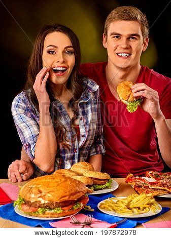 Couple eating fast food. Man and woman eat hamburger with ham. Friends holding two burder junk on dark background isolated. Table with hamburgers and fried potatoes.