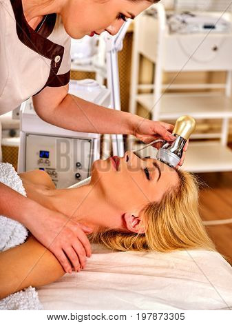 Skin resurfacing facial procedure on ultrasound face machine. Acne treatment for woman receiving electric lift massage at spa . Electronic stimulation muscles. Comfort and convenience in beauty salon.