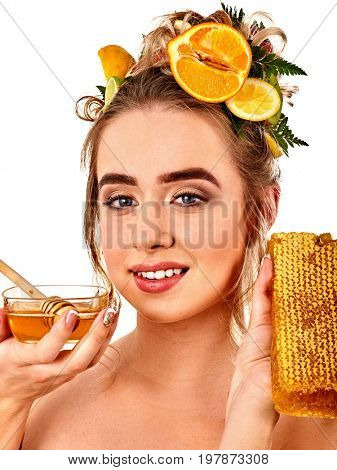 Honey facial mask with fresh fruits for hair and skin on woman head. Girl with beautiful face hold honeycombs for homemade organic skin and hair therapy. Means for accelerating hair growth.