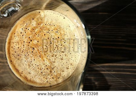 Jug with cold brew coffee and froth on table, closeup