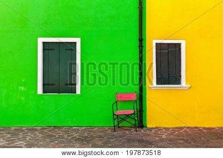 Two windows shuttered and outer wall of the house painted in vivid green and yellow colors in Burano, Italy.