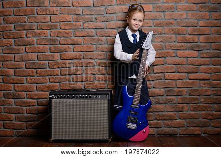 Modern little girl in school uniform posing with electric guitar over brick wall background. Rock star, rock music, pop music concept.