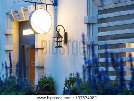 exterior of a store with a vintage lamp and round blank signboard,blue flowers.