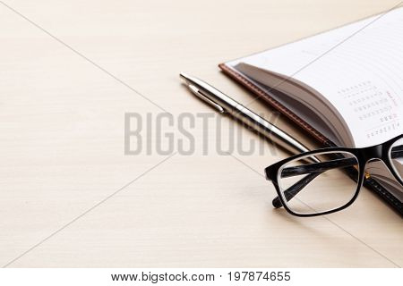 Wooden office desk with supplies. Notepad, pen and glasses. With space for your text