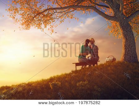Happy couple in love. Stunning sensual portrait of young stylish fashion couple picnicking together near a tree in autumn park.