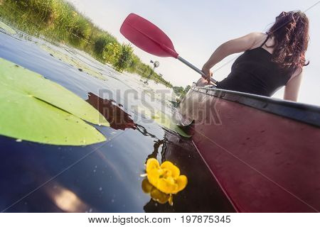 Woman sitting in a Kayak peddling on a calm river with green shores and yellow lily's