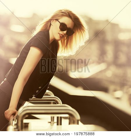 Happy young fashion woman in sunglasses walking in city street at sunset. Stylish female model in black jacket outdoor