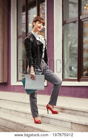 Happy young fashion business woman with a folders walking in city street. Stylish female model in black leather jacket outdoor