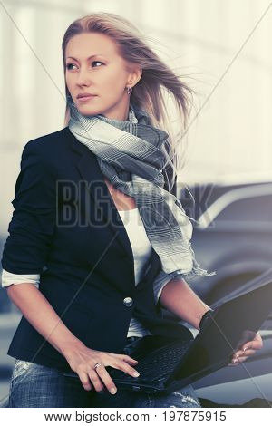 Young fashion business woman with laptop sitting on her car Stylish female model blue jacket and scarf outdoor