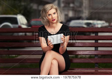 Young blond woman with tablet computer sitting on bench. Stylish fashion model in black dress in a city street