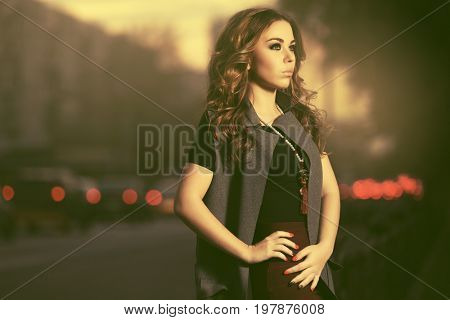 Young woman with long curly hairs walking in a night city street. Stylish fashion model in sleeveless coat outdoor
