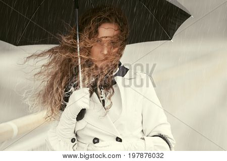 Beautiful woman with umbrella walking in city street. Stylish fashion model with long curly hairs in white coat outdoor