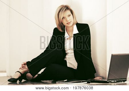 Young business woman with laptop sitting at the wall. Stylish fashion model in black suit outdoor