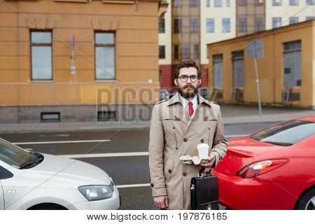Jobless man with drink on background of cars and road