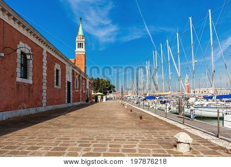 Promenade along moored yachts and belfry of San Giorgio Maggiore church on background under blue sky in Venice, Italy.