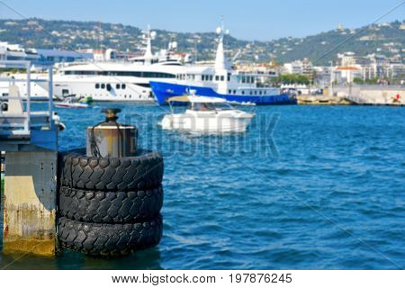 a view of the Port of Cannes, in the French Riviera, with a rusty dock in the foreground and some unrecognizable moored yachts in the background