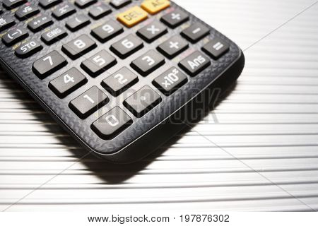 Scientific calculator close up on a metal table.