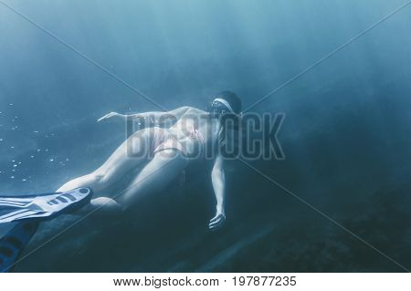 Young woman free diving in deep blue sea wearing in mask snorkel and flippers rear view.