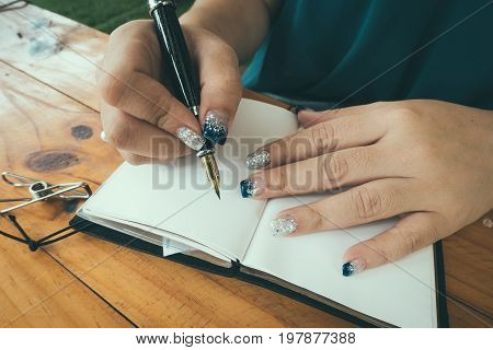 Woman sitting at the table writing in the notebook in nice light home interior. Working at home. Freelancer. writing down ideas. indoors. vintage filtered image.