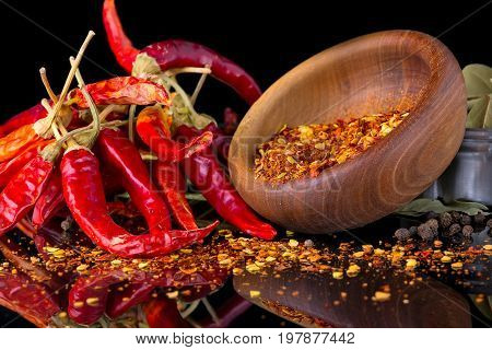Red chili peppers and chili flakes on a black background with reflection close-up
