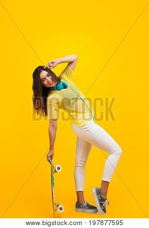Side view of trendy teenager with headphones and posing with longboard on orange background.