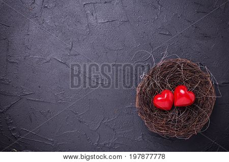 Hearts in nest on black slate background. Flat lay.Top view. St. Valentine day background. Place for text.