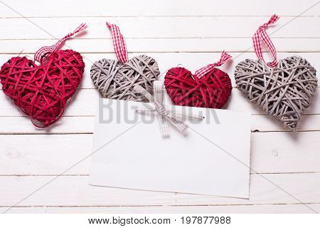 Border from red and grey decorative hearts and empty tag on white wooden background. Selective focus. Place for text. Top view.