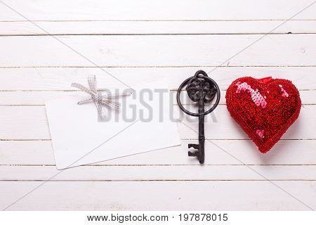 Red shiny decorative heart empty tag and key on white wooden background. Selective focus. Place for text. Top view.