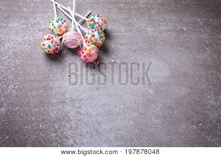 Colorful cake pops can on grey slate background. Selective focus. Place for text.