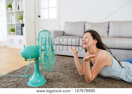 beautiful young woman enjoying electric fan cool wind in living room.